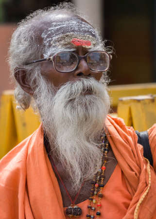 sadhu: Trichy, India - October 15, 2013: Old, graying sadhu with beard and glasses. Wears orange garb and has his forehead smeared with white and red. Seen in Anna Mandapam. Editorial