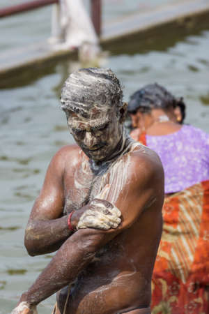 Trichy, India - October 15, 2013: During ritual bathing in the Cauvery River at Amma Mandapam, a dark skinned man had become white due to the abundance of soap he uses.