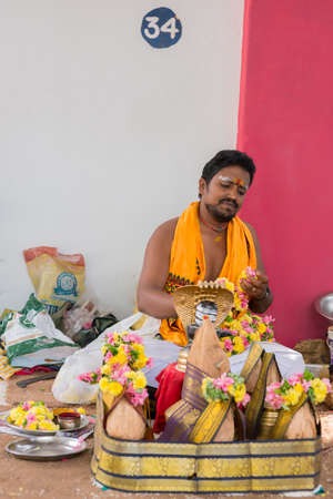 dhoti: Trichy, India - October 15, 2013: Young Guru #34 sits in line and waits for clients at Amma Mandapam. A basket with offerings to be bought stands in front. He wears a white dhoti and an orange shawl. A golden statue of a five-headed cobra stands nearby.