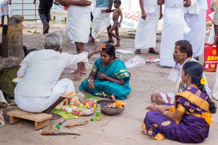 conceiving: Trichy, India - October 15, 2013: Religious ritual to promote conceiving and pregnancy at Amma Mandapam. Offerings have been made, a flame has been lighted and family members watch. Here, the guru touches the head of the young woman with an orange, simpli Editorial