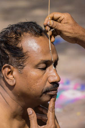 vishnu: Trichy, India - October 15, 2013: Closeup of mans face while a guru paints the Vishnu symbol in white on the mans forehead at Amma Mandapam. This is part of a religious ritual performed by guru. Editorial