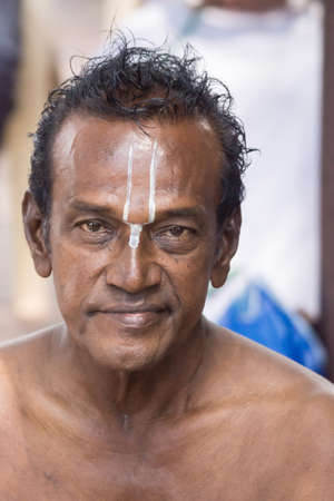 vishnu: Trichy, India - October 15, 2013: Closeup of mans face with white Vishnu symbol on his forehead, painted by guru at Amma Mandapam. This is part of a religious ritual performed by guru.
