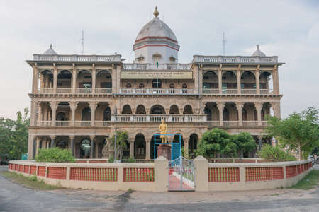 deposed: Chettinad, India - October 15, 2013: Old mansion of the deposed maharajah is now the government building that houses the local tax collectors. Golden majarajah statue in front.
