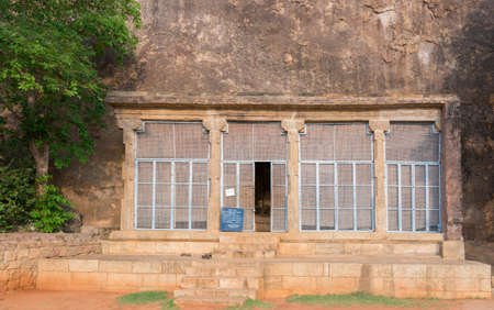 idols: Chettinad, India - October 15, 2013: Chithannavasal Cave Jain Temple is hewn into a huge rock. A screen fills a pillared gate in front of the cave opening; the only thing visible from outside. Editorial