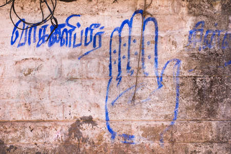 national congress: Chettinad, India - October 16, 2013: The blue hand symbol of India National Congress Party is painted on a beige, brown wall with words in Tamil.