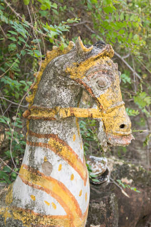 devotions: Chettinad, India - October 16, 2013: Ayyanar, village protector, Horse shrine of Namunasamudran. Old clay horse head with yellow gear and blackened by mold. Editorial