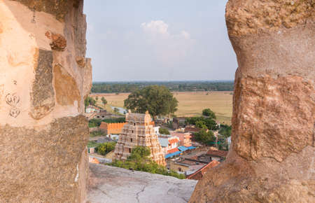 garrison: Chettinad, India - October 16, 2013: View out of Thirumayam Fort through one battlements opening upon village and temple gopuram. Editorial