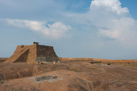 bulwark: Chettinad, India - October 16, 2013: A pyramid with cannon stands on top of plateau at the Thirumayam fort. The rampart and battlements form a line under blue skies.