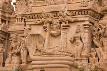 lies down: Chettinad, India - October 16, 2013: Detail of Shiva temple in Thirumayam. Lord Vishnu lies down on the coil of a five headed snake. Image is called Ananta Shesha, or Ranganatha.