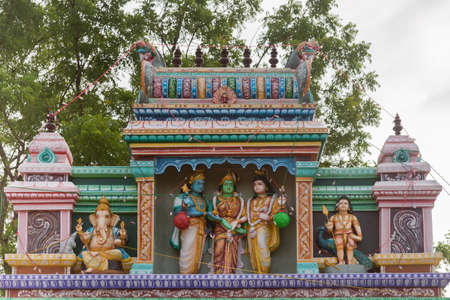 parvati: Chettinad, India - October 17, 2013: Entrance to the shrine of Shani, known as Satan in the West, in Kadiapatti. Image features wedding of Shiva and Parvati. The blue skinned person is Lord Vishnu giving his sister, the green-skinned female in the middle, Editorial