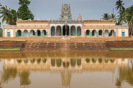 Chettinad, India - October 17, 2013: Closeup of Kothamangalam Shiva Temple reflected in temple pond filled with brown water. Vimanam tower in teh back. Green trees. All against blue sky. Banco de Imagens