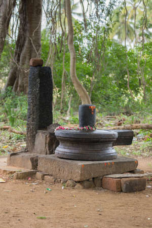 vulva: Chettinad, India - October 17, 2013: Closeup of black Shivalingam standing in vulva in a forest shrine near Kothamangalam. Foreground brown dirt. Background green forest.