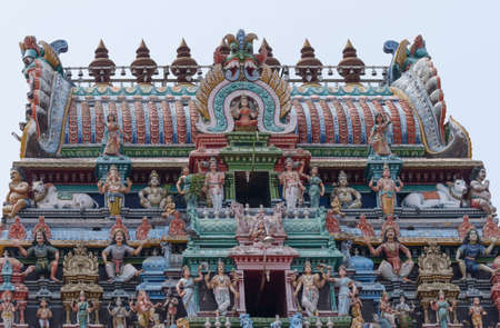 parvati: Chettinad, India - October 17, 2013:The Kalasha, the top of Gopuram at Shiva temple in Kottaiyur. Loaded with Hindu-themed colorful statues with Lakshmi on top and center.