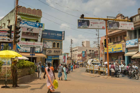 motorcycle officer: Chettinad, India - October 17, 2013: Busy intersection in Karaikudi city shows police, traffic, people, billboards, motorbikes, shops, and more.