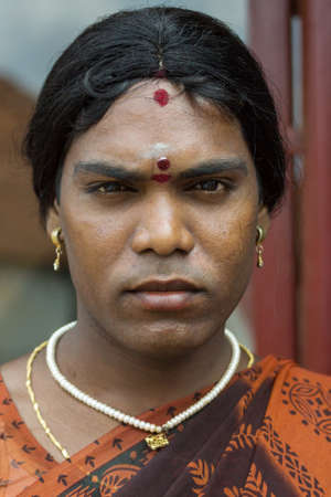 Chettinad, India - October 17, 2013: Portrait of Ms. Abinaja, a Hijra, a transgender person, a male that dresses and acts like a woman, and has a sacred status in Hinduism. Dark, stern face and jewelry. Karaikudi city.