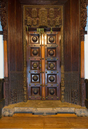 chiseled: Chettinad, India - October 17, 2013: Chidambara Palace in Kadiapatti. Massive wooden dark brown antique door set in frame of hand chiseled wood. Mango leaves have spiritual and healing powers.