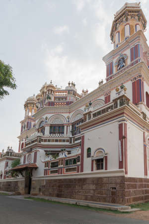 purples: Chettinad, India - October 17, 2013: Chidambara Palace in Kadiapatti. Corner view on facade shows towers, balconies, balustrades, the front entrance, Krishna decorations. Mainly beige and purples Editorial