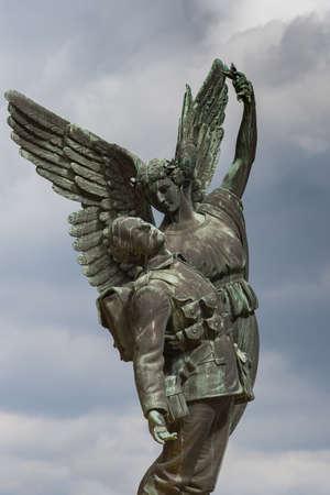 Vancouver, Canada - 23 juli 2016: Bronzen beeld van de engel het dragen van een dode soldaat naar de hemel. Het herdenkt de Canadian Pacific Railway werknemers die in WO I en WO II stierf. Alleen de achtergrond is de gemengde gekleurde hemel. Redactioneel