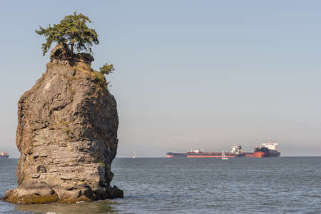 Vancouver, Canada - July 24, 2016: Siwash Rock with a number of black-white-red waiting sea vessels waiting to come into the harbor. Clear skies.