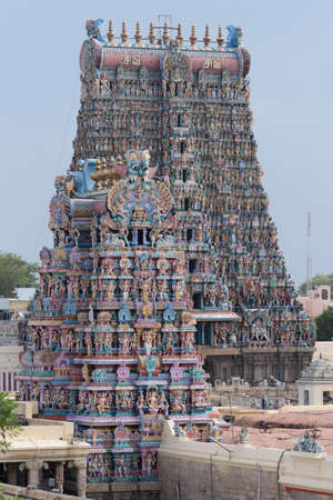 Closeup of the South Gopuram of the Meenakshi Temple against faint blue sky. Partly hidden by the Vimanam of the temple proper.