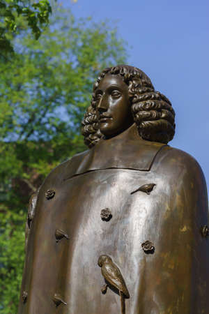 sephardi: Amsterdam, the Netherlands - August 16, 2016: The famous philosopher Baruch Spinoza has his statue near the Bijvoetbrug. Bronze shows serious looking man with long curly hair.