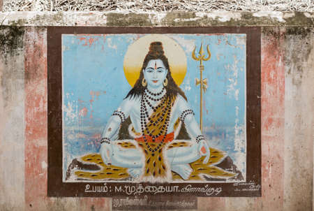 tiger skin: At Pandi Kovil, the wall painting shows a sitting, blue Lord Shiva holding a trident and a halo while dressed in tiger skin.