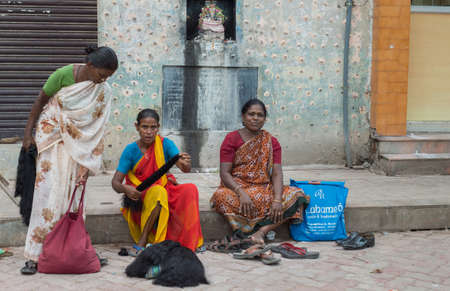 peddle: Madurai, India - October 19, 2013: Three women sell black human hair out of bags while sitting on the sidewalk near the Meenakshi Temple. All wear saris.