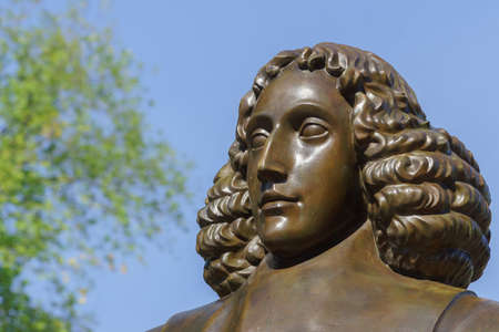 sephardi: Amsterdam, the Netherlands - August 16, 2016: The famous philosopher Baruch Spinoza has his statue near the Bijvoetbrug. Detail of bronze shows serious looking man with long curly hair. Editorial