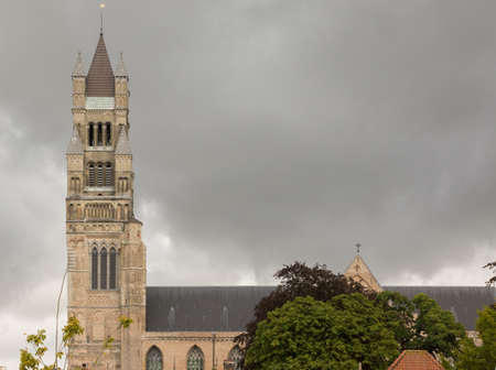 imminent: Brugge, Belgium - August 10, 2016: The tower of the Sint Salvator Cathedral and part of the roof. Dark clouds of an imminent rainstorm gather above the church. Dark green trees add new colors. Stock Photo