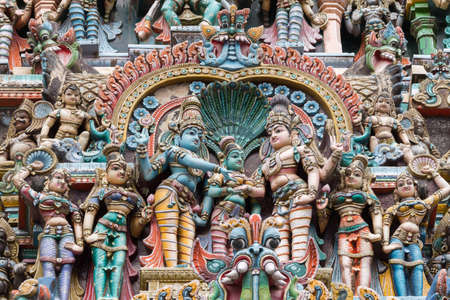 Madurai, India - October 19, 2013: Closeup of the wedding scene of Meenakshi and Shiva, while Vishnu gives his sister away. Facade of West Gopuram at Meenakshi Temple. Other figures in landscape photo.