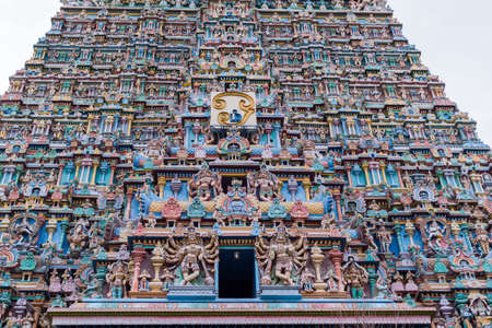 goddesses: Madurai, India - October 19, 2013: Part of the East Gopuram of the Meenakshi Temple fills entire photo. Abundance of pastel colored statues of gods, goddesses and more.