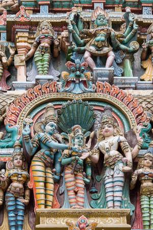 vishnu: Madurai, India - October 19, 2013: Closeup of the wedding scene of Meenakshi and Shiva, while Vishnu gives his sister away. Facade of West Gopuram at Meenakshi Temple. Devi Kali and other statues in photo. Stock Photo