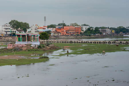 pedestrian bridges: Madurai, India - October 19, 2013: Broad view on shallow Vaigai river with empty Meenakshi shrine and pedestrian bridge. Horses and people in the photo.