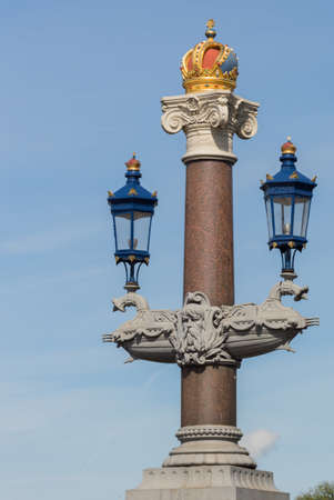 amstel: Amsterdam, the Netherlands - August 16, 2016: One of the decorative pillars and light poles on the Blauwbrug over the Amstel River is topped off by a golden crown. Stock Photo