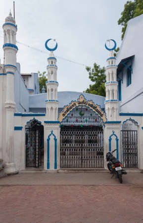 sunni: Madurai, India - October 21, 2013: Entrance with four short minarets to the Kajimar Mosque is painted white and blue. Black and white iron fence forms the gate,