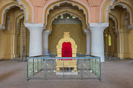 viceroy: Madurai, India - October 21, 2013: Copy of the golden throne of the Nayak at main audience hall of his palace. Fence shields throne from public.