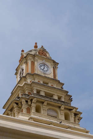 Madurai, India - October 21, 2013: The clock tower of the Nayak Palace against blue sky. Dials show seven o�clock.