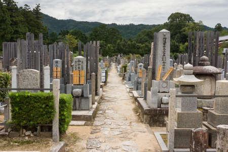 Kyoto, Japan - September 15, 2016: Adjacent to the Shinnyo-do Buddhist Temple is a large cemetery serving the Buddhist community. Long alley with the classic Japanese tombstones leads to the woods. Mountains in the back.