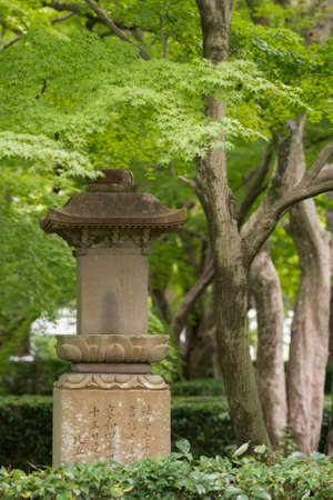philosophic: Kyoto, Japan - September 15, 2016: At the Shinnyo-do Buddhist Temple the stone statue of a lantern stands in the garden surrounded by green trees. Stock Photo
