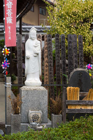 philosophic: Kyoto, Japan - September 15, 2016: White Quan Yin with child statue at Koanin Buddhist Temple. She stands on a pedestal and is surrounded by plenty of wooden memorial planks.