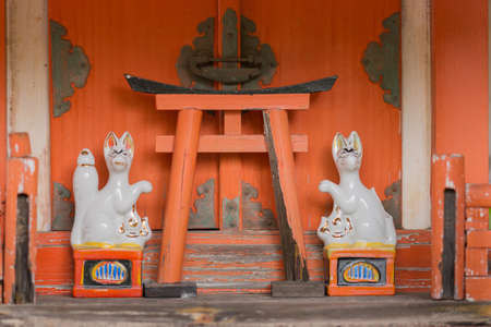 Kyoto, Japan - September 15, 2016: Orange colored altar with two white porcelain foxes and one Torii at Koanin Shinto shrine. Fox is considered the messenger between here and the afterlife.