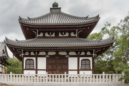 Kyoto, Japan - September 15, 2016: Smaller hall at Kurodani Buddhist Temple. Dark brown wood structure combines with snow white walls. Storm clouds and some green trees. Editorial