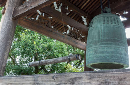 proclaim: Kyoto, Japan - September 15, 2016: The giant, green metal bell hangs in pagoda at Kurodani Buddhist Temple. Dark brown wood structure and some green trees.