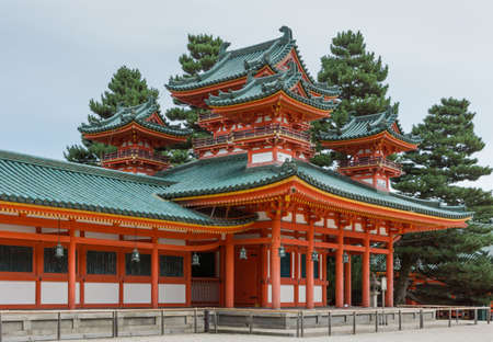 Kyoto, Japan - September 15, 2016: Vermilion structure with green roofs, consists of ground level with four elaborate towers on top in view. Gray skies and green trees. Editorial