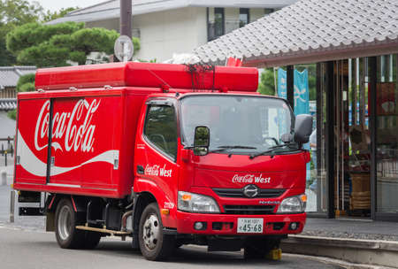 retailer: Kyoto, Japan - September 16, 2016: One of the red Coca-Cola delivery trucks in front of retailer in the street. Iron fence on top holds the bags full of empty recycled bottles.