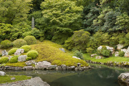 obelisk stone: Kyoto, Japan - September 16, 2016: Part of the formal garden at Shorenin Buddhist Temple comes in several shades of green with a pond and a stone obelisk.