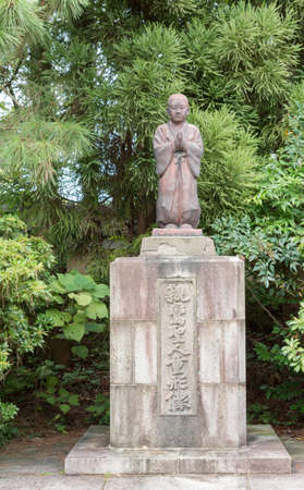Kyoto, Japan - September 16, 2016: Boyish looking Bodhisvattva reddish statue stands in the formal garden of Shorinin Buddhist Temple. Boy is known as Sudhana or red boy, who is seduced by Guanyin.