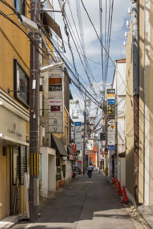 entanglement: Kyoto, Japan - September 16, 2016: Street in Gion neighborhood houses multiple bars on top of each other. The entanglement of power and communication cables is standard in Kyoto. Editorial
