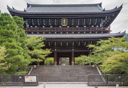 Kyoto, Japan - September 16, 2016: The wooden monumental gate to Chion-in Buddhist Temple in the largest one of its era in Japan. Flanked by trees under cloudy sky.