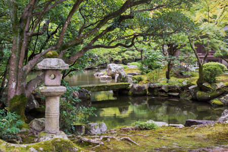 hojo: Kyoto, Japan - September 16, 2016: View of the Hojo Garden at Chion-in Buddhist temple. Pond, bridge, lantern and lots of green plants and trees.